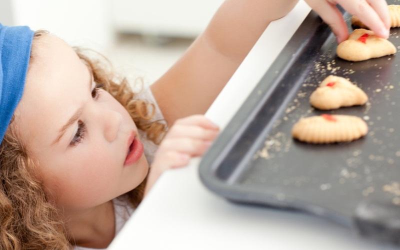 Очаровательная маленькая девочка берет печенье с противня